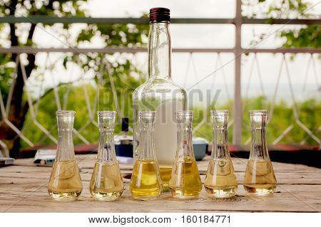 Bottle Of Plum Brandy With Small Glasses On Wooden Table