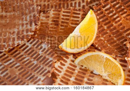Two Lobules Of Orange On A Background Of Crispy Waffles Две дольки апельсина на фоне хрустящих вафел
