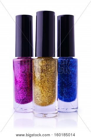 Set of multicolored shiny nail polish with glitter. Golden blue and purple nail polish isolated on white.