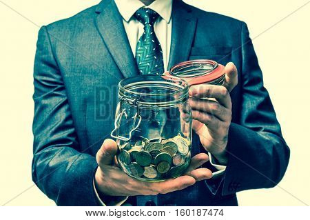 Man In Black Suit Holding Money Jar With Coins - Retro Style