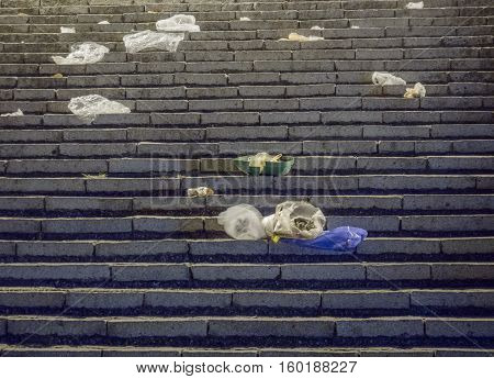 Picture of a granite stairs close up. Granite stairs pattern close up. A lot of rubbish are laying on the granite stars. Background of granite stairs - front view.