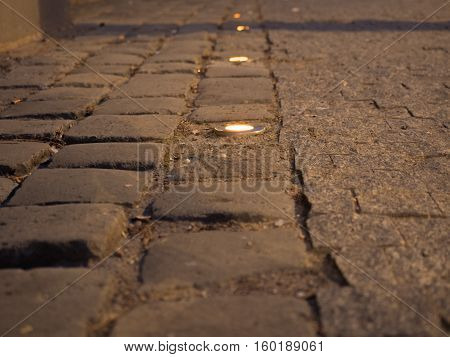 Picture of the cobblestone paved road with spotlight close up. Dark brown cobblestone road pattern close up. Selective focus on the middle of the picture.