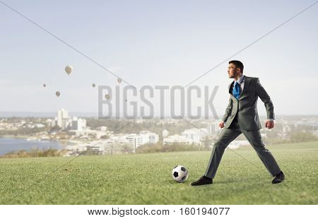 Businessman kicking soccer ball . Mixed media