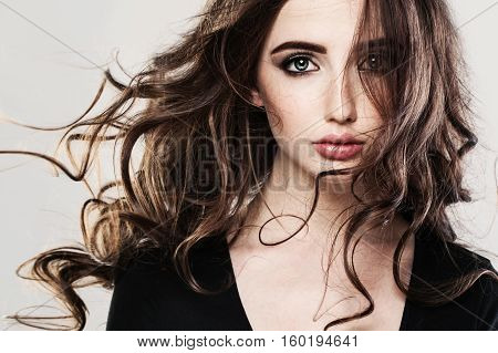Glamorous Brunette Woman with Curly Hairstyle. Long Brown Hair. Motion
