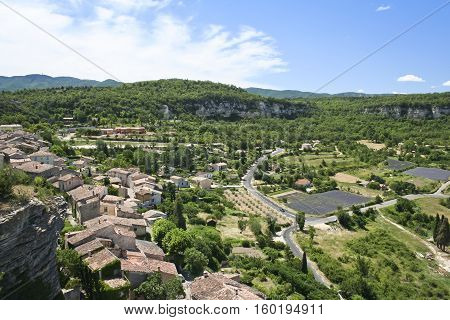 traditional hillside village in provence france overlooking blooming fields of lavender flowers