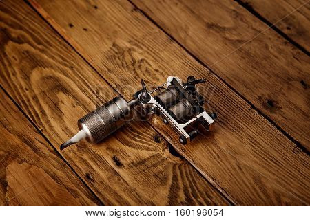 Tattoo Gun On A Rustic Wooden Table