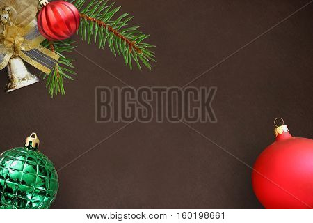 Christmas fir branch red wavy dull and green ribbed ball bell on a dark background