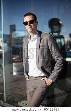 Male adult man in suit standing with hands in the pockets of the trousers next to the big reflective window outdoors on sunny day, handsome caucasian model