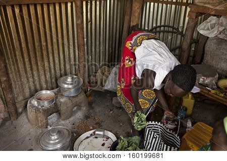 BOR, SOUTH SUDAN, FEBRUARY 26, 2013: A woman cooks using traditional methods over a small charcoal oven in South Sudan. Charcoal is the only method of cooking in this region.