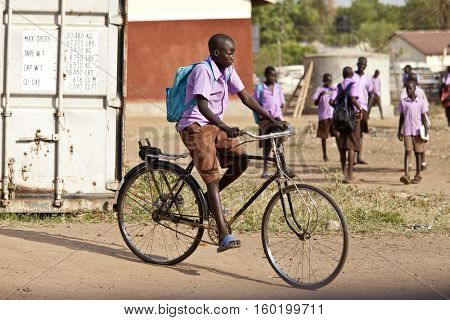 TORIT, SOUTH SUDAN-FEBRUARY 20, 2013: Unidentified student rides his bicycle from school in the village of Torit, South Sudan