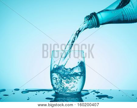 Bottle with creative splashing water on blue background.