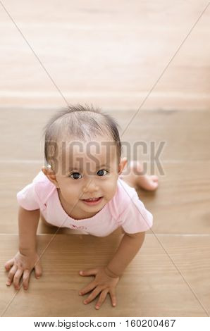 Beautiful smiling asian baby girl while crawling up a stair. Happy baby with teeth.