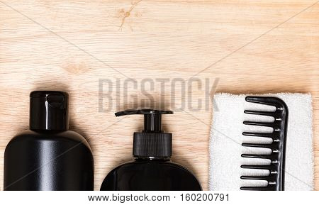 Hair care and styling background. Hair beauty products, wide tooth comb, towel on natural wood surface. Copy space