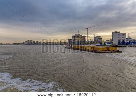 Shot from the ferry whist crossing over the River Thames at Woolwich. Shows a tug pulling a load of containers downriver.