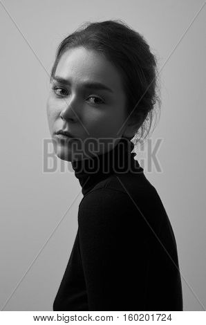 Dramatic Black And White Portrait Of Young Beautiful Girl With Freckles In A Black Turtleneck On Whi