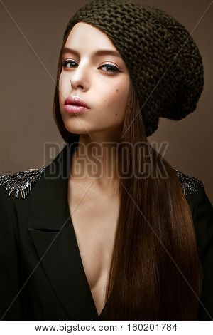 Beautiful girl in winter knit hat and khaki jacket. Young model with gentle make-up and colored arrows. Warm winter picture. Beauty face.