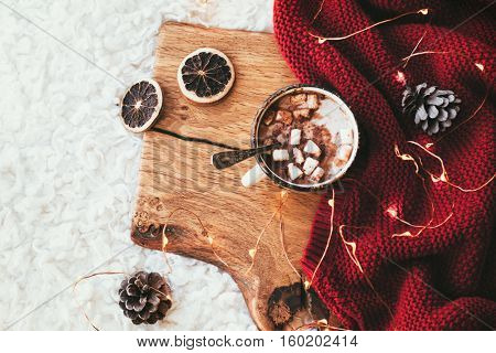 Winter homely scene. Warm knit blanket and cup of sweet cocoa with marshmallows on wooden tray in bed. Lazy cold weekend.