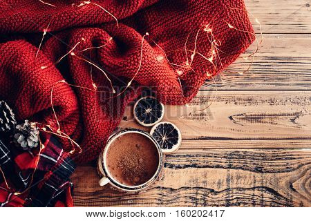 Winter homely scene. Warm knit blanket and cup of hot cocoa, led lights string. Christmas holiday decor.