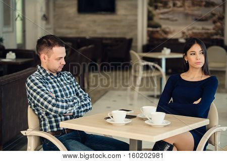 Young unhappy married couple having serious quarrel at cafe.