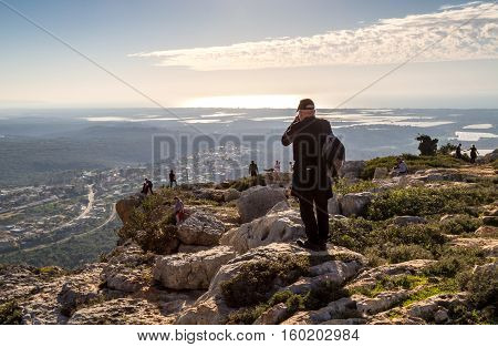 UPPER GALILEE ISRAEL - JANUARY 16: Mountain landscape in sunset light people stand on a mountain top mountainous area of Upper Galilee Israel on January 16 2016