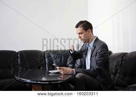 Male adult businessman sitting behind smal oval dark shiny table on a black leather sofa. Man is holding coffee cup in one hand and cellphone in other hand. Looking down on the phone.