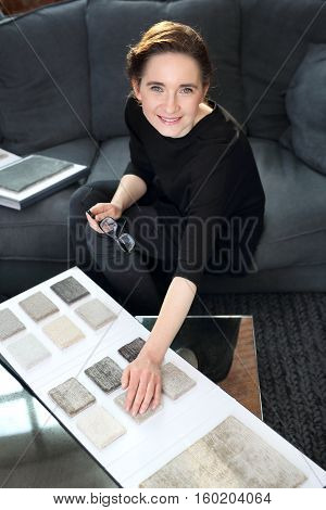 Interior decorating, shopping carpet. Arranging home shopping coverings. Woman chooses carpet for the living room