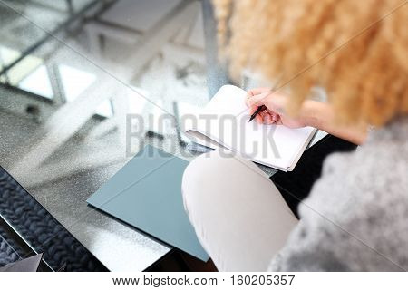 Business woman recorded expenses. Girl taking notes while sitting on the sofa