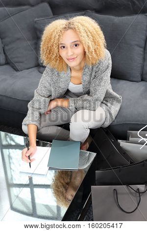 Girl taking notes while sitting on the sofa Shopping. Girl taking notes while sitting on the sofa