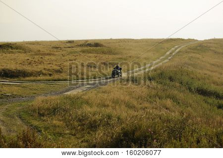 Man rides quad bike quadricycle four wheeler on cart road along field on mountain scene