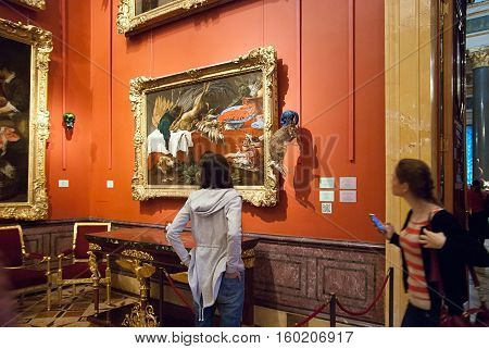Saint-Petersburg, Russia, December 1, 2016: People look at the stuffed rabbit with scull near painting in The State Hermitage Museum. Exhibit of temporary modern art exhibition