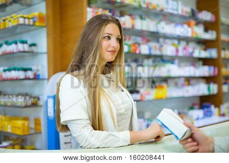 Attractive smiling pharmacist giving her client pills at the local drugstore.