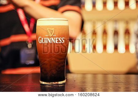 Pint of guinness with one person at the background selective focus - 17.july 2012