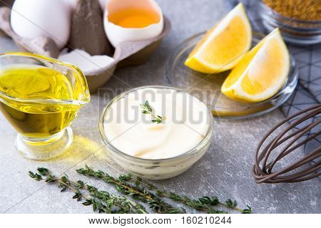 Fresh Homemade White Sauce Mayonnaise And Ingredients Eggs, Lemon Olive Oil On Stone Background.