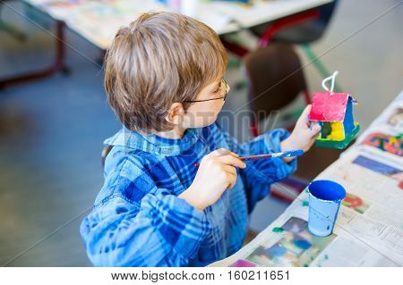 Little school kid boy with glasses coloring bird house with watercolors in labor classroom. child having fun with learning, building skills, education. Primary school and pupil.