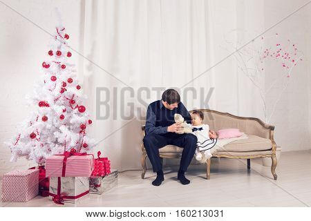 family children christmas x-mas love concept - happy father with adorable baby daughter near christmas tree.