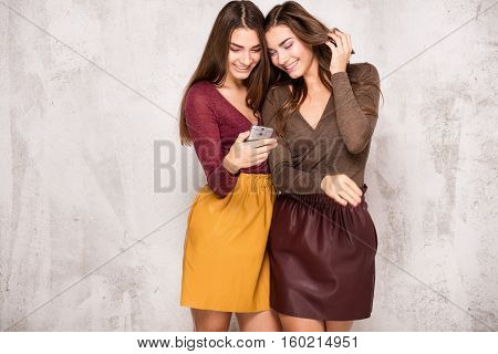 Beautiful Young Twins Using Mobile Phone.
