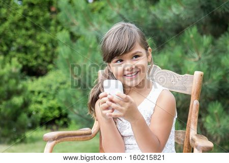 Smiling long haired brunette little girl is sitting on and old wooden chair outdoors. Little girl is holding a smart phone in her hands. All potential trademarks and buttons on smart phone are removed.