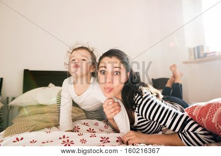 Beautiful young mother having fun with her cute little daughter on bed in her bedroom, sticking tongues out
