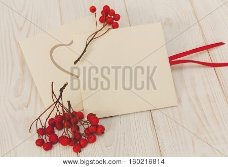 Empty envelopes with red rowan and stripe.White wooden table.Empty space for text