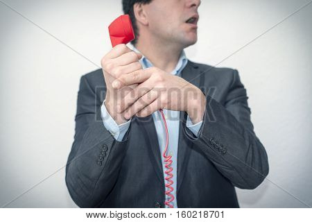 Young businessman can't believe what he is hearing on the phone. The Boss informs him he screwed up!