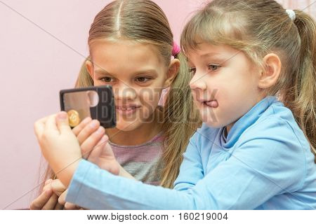 Two Children Considered A Coin Through A Magnifying Glass