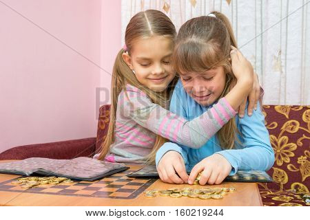 The Older Sister Comforting Crying Younger Sister, Which Collects A Stack Of Coins