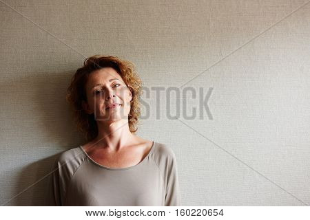 Woman Standing Inside With Pensive Expression
