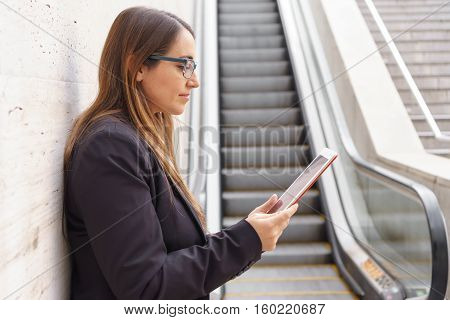 Closeup view of office woman standing with tablet and glasses near scalator, profile view