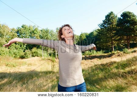 Happy Older Woman Standing Outside With Arms Outstretched