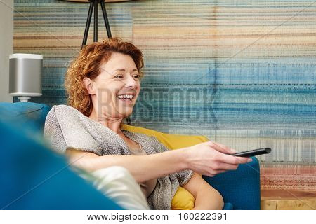 Happy Older Woman Changing Channel On Television