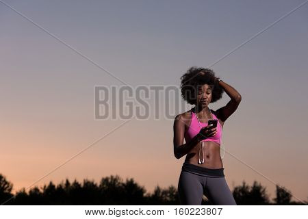 portrait of a young beautiful african american woman with headphones and mobile phone jogging in nature beautiful summer night