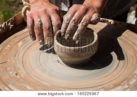 Hands working on the pottery wheel closeup
