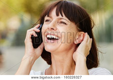 Laughing Older Woman Talking On Smart Phone Outside