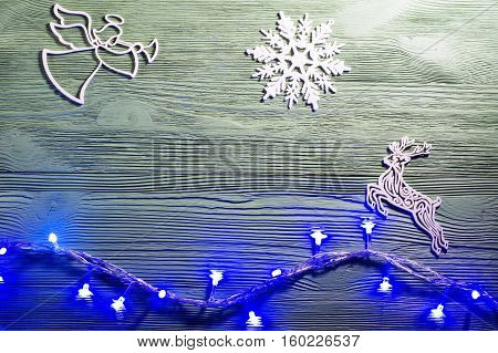 Christmas angel with wings and trumpet on cloud heralds the arrival of Christmas. Angel reindeer and snowflakes on wooden background flat lay. Christmas background with garland lights